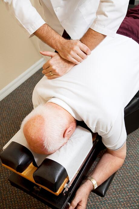 Chiropractor Adjusting Man with Back Pain