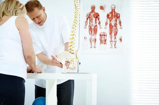 Chiropractor-explains-patient-using-plastic-model-000064837281_Medium.jpg