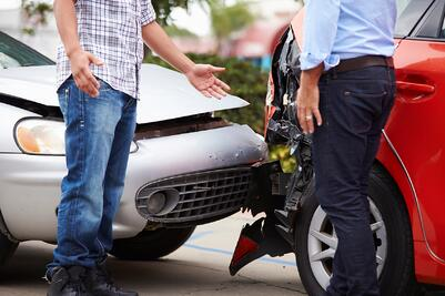 two men in Iona trading insurance information after a car crash